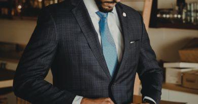 man buttoning a custom suit