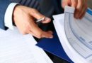Male arm in suit offer insurance form clipped to pad and silver pen to sign closeup