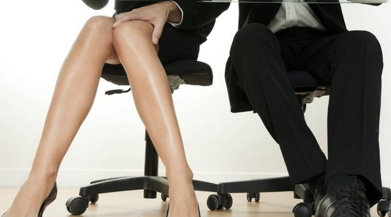 man touching woman's leg in the office